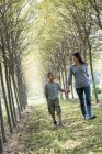 Woman with son walking in woods. — Stock Photo