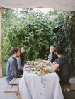People seated at a table in the garden. — Stock Photo