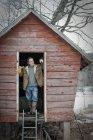 Man standing in doorway of henhouse. — Stock Photo