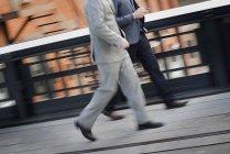 Businessmen walking along city sidewalk — Stock Photo