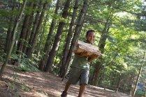 Muchacho llevando leña a través de los bosques - foto de stock