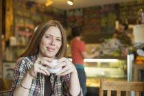 Mulher sentada no café e café — Fotografia de Stock
