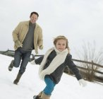 Man chasing a young girl in the snow — Stock Photo