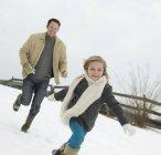 Mann jagt ein junges Mädchen im Schnee — Stockfoto
