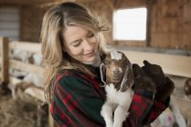 Woman cradling young goat — Stock Photo