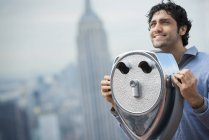 Hombre mirando a través de un telescopio sobre la ciudad - foto de stock