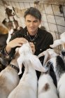 Man in a barn with goats — Stock Photo