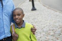 Menino, segurando o saco, ao lado de seu pai — Fotografia de Stock