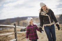 Donna e bambino che camminano in una fattoria — Foto stock