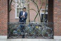 Uomo in vestito mezzo dello smart phone — Foto stock