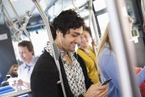 Man checking phone on a city bus — Stock Photo