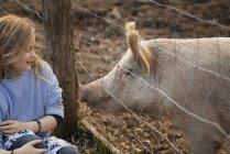 Свиня в паддоках, дивлячись на молодій дівчині. — стокове фото