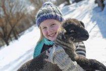 Mädchen hält ein junges Lamm. — Stockfoto