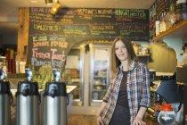 Donna che si appoggia sul bancone, dalla macchina del caffè — Foto stock