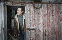 Man at open barn door. — Stock Photo