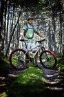 Человек с горным велосипедом в лесу — стоковое фото