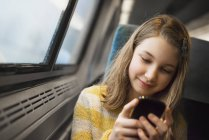 Blonde girl sitting by window on train — Stock Photo