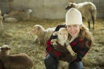 Frau hält ein kleines Lamm. — Stockfoto