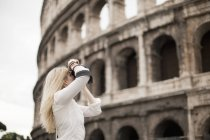 Woman taking photographs of Colosseum — Stock Photo