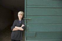 Rapaz encostado a uma porta do celeiro — Fotografia de Stock