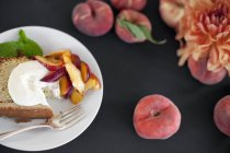 Plate with creme fraiche cake and peaches — Stock Photo