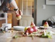 Peras orgánicas frescas que sumerge en una salsa - foto de stock