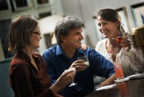 Women and a man sitting at a bar. — Stock Photo