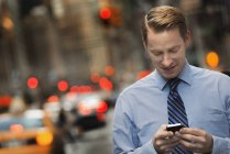 Man with cell phone on a busy street — Stock Photo