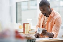Man at breakfast bar with cup of tea. — Stock Photo