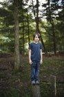 Boy standing on a narrow tree trunk — Stock Photo