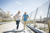 Men jogging along a bridge. — Stock Photo