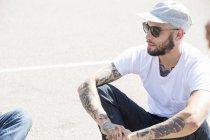 Junger Mann mit Tattoos auf dem Boden sitzend. — Stockfoto