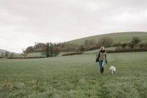 Mulher andando com um cão — Fotografia de Stock