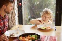 Bambino e un uomo seduto a un tavolo — Foto stock
