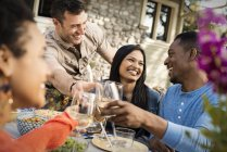 People laughing and clinking wine glasses — Stock Photo