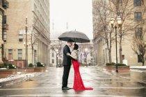 Casal beijando sob um guarda-chuva na cidade — Fotografia de Stock