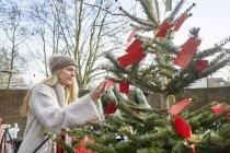 Donna che legge messaggi sull'albero di Natale — Foto stock