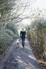 Женщина гуляет с собакой — стоковое фото