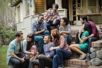 Friends sitting on the steps of a house porch — Stock Photo