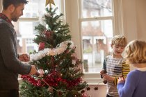Family decorating a Christmas tree at home. — Stock Photo