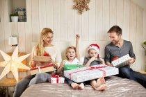 Семья, сидя в постели на утро Рождества — стоковое фото