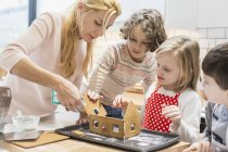 Family creating a baked gingerbread house. — Stock Photo