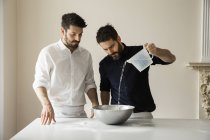 Bakers pouring water into bowl. — Stock Photo