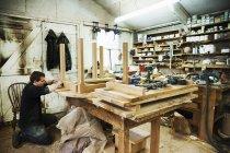 Людина, що працює над плінтусом дерев'яний стіл — стокове фото