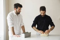 Two bakers standing at a table — Stock Photo