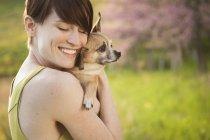 Женщина держит маленькую собачку чихуахуа — стоковое фото