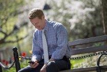 Businessman sitting on park bench — Stock Photo