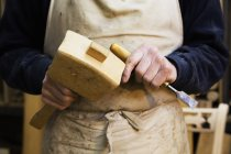 Man holding a wooden mallet and chisel. — Stock Photo