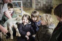 Agricultor e crianças com cordeiro recém-nascido — Fotografia de Stock
