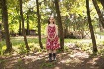 Menina de pé no arvoredo de árvores — Fotografia de Stock
